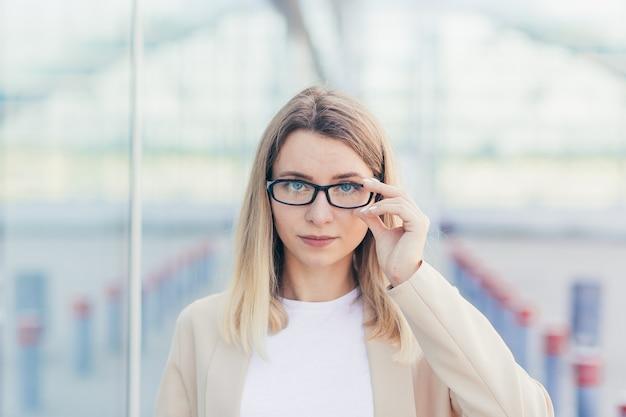 Portret van een serieuze zakenvrouw, met een blonde bril die naar de camera kijkt