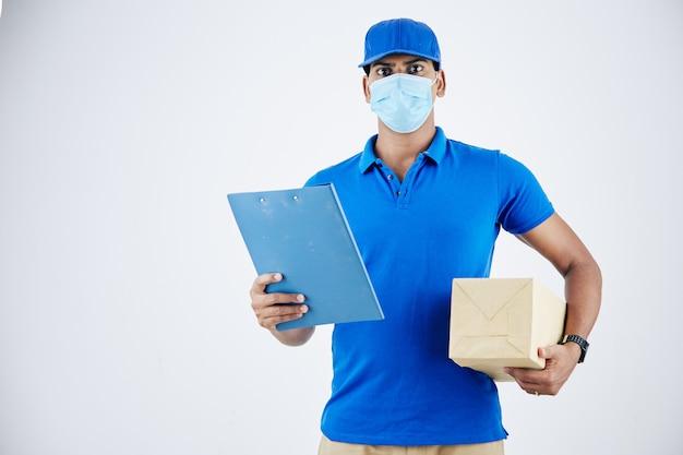 Portret van een serieuze zelfverzekerde jonge bezorger met een medisch masker met document en pakket