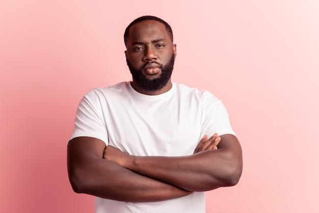 Portret van een serieuze zelfverzekerde man, een strikte camera met gekruiste armen op een roze muur