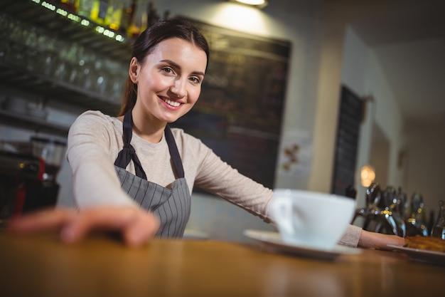 Portret van een serveerster die zich bij teller