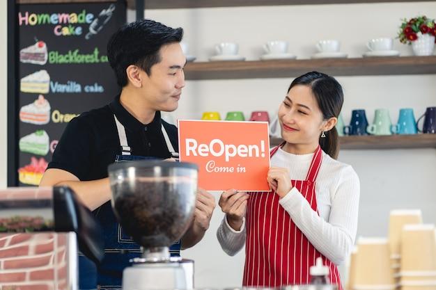 Portret van een serveerster van een man en een vrouw die aan de poort van haar coffeeshop staat met gesloten uithangbord