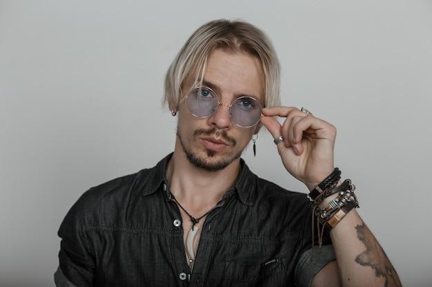 Portret van een sexy bebaarde jongeman met een stijlvol kapsel met lederen armbanden in een modieus shirt in de buurt van de muur in de kamer.