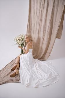 Portret van een sexy blonde in een mooie witte jurk in de buurt van een vaas met wilde bloemen