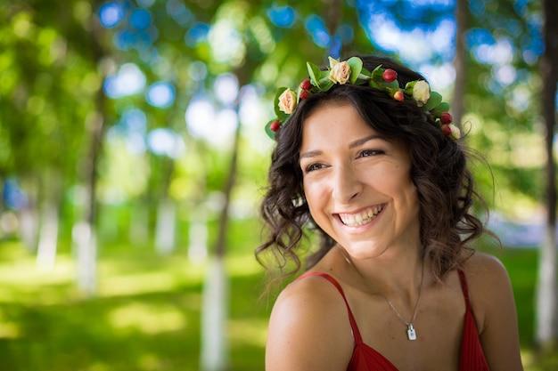Portret van een sexy brunette met bloemen in haar haar in een groen park. meisje lente.