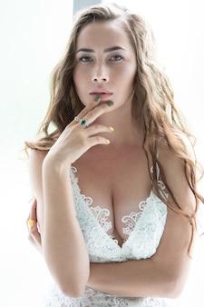 Portret van een sexy jong meisje in kanten ondergoed dat haar hand aan haar lippen raakte