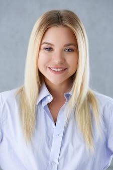Portret van een sexy vrouw in een man shirt dragen op een grijze achtergrond kijkt naar de camera en glimlachen kijken advies te geven wil bezwaren worden niet geaccepteerd.