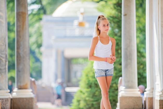 Portret van een slank jong tienermeisje op de achtergrond van antieke architectuur in het park