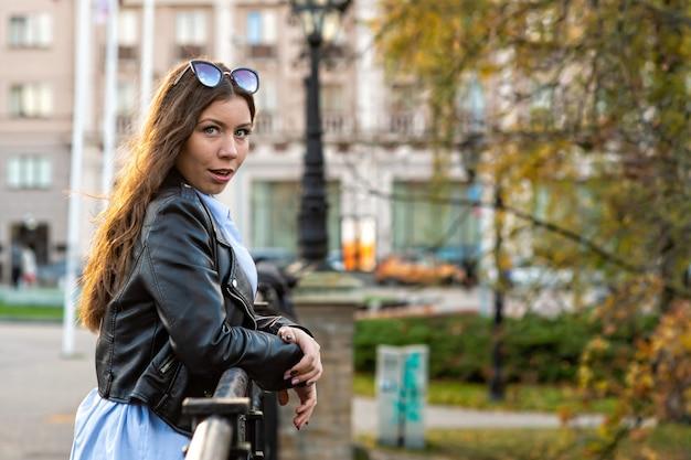 Portret van een slanke emotionele donkerharige tiener vrouw in een stadspark op een zonnige dag