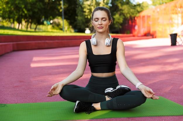 Portret van een slanke, sportieve vrouw die een trainingspak draagt en mediteert op een fitnessmat in lotushouding terwijl ze yoga beoefent in een groen park