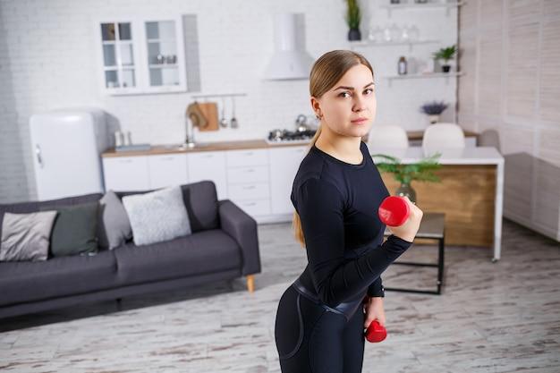 Portret van een slanke vrouw gaat thuis sporten, op haar top en fitnesskleding in leggings. thuis fitnessen voor een mooi lichaam. oefeningen met dumbbells voor het vrouwelijk lichaam