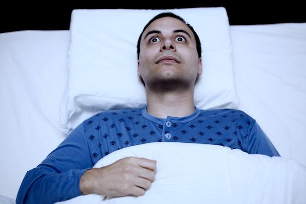 Portret van een slapeloosheidsmens die in zijn bed probeert te slapen