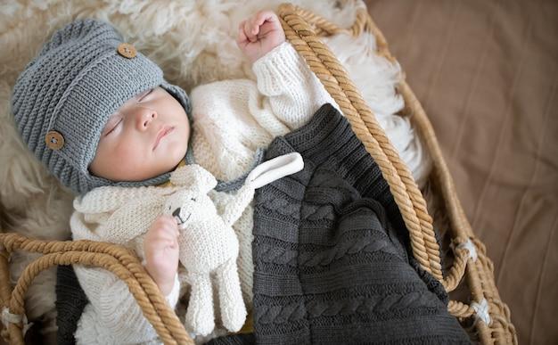 Portret van een slapende baby in een rieten wieg in een warme gebreide muts onder een warme deken met een speeltje in het handvat.