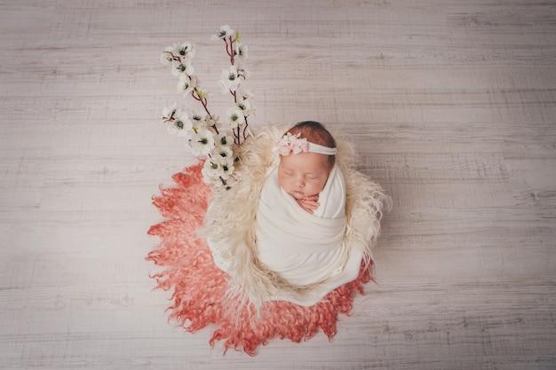 Portret van een slapende pasgeboren baby. imitatie van een baby in de baarmoeder. bloemen als decoraties, interieur.