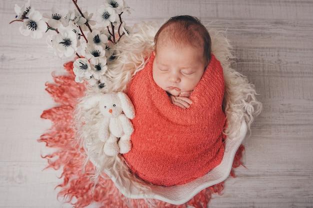 Portret van een slapende pasgeboren baby. imitatie van een baby in de baarmoeder. bloemen als versiering