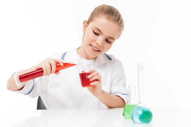 Portret van een slim meisje in een witte laboratoriumjas die chemische experimenten maakt met veelkleurige vloeistof in reageerbuizen die over een witte muur worden geïsoleerd
