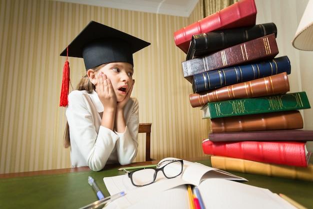 Portret van een slim meisje met een afstudeerpet die naar een grote stapel boeken op tafel in de bibliotheek kijkt