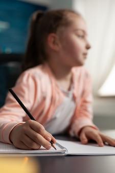 Portret van een slim schoolmeisje dat luistert naar een online klasvergaderleraar en aantekeningen maakt voor lesinformatie. kind leert van studieboek dat thuisonderwijs krijgt voor onderwijskennis
