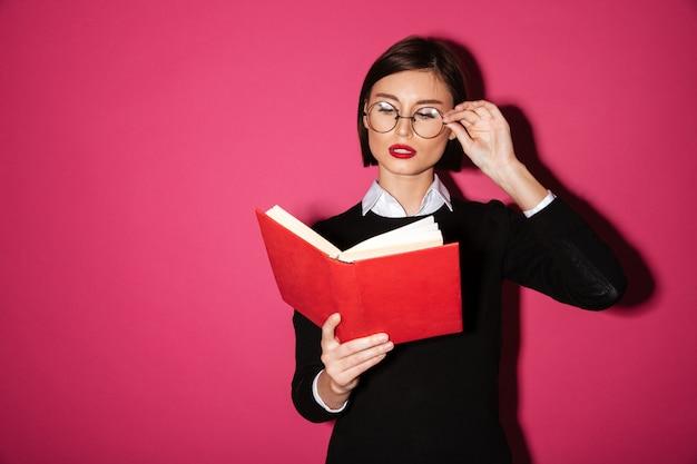 Portret van een slimme aantrekkelijke onderneemster die een boek leest