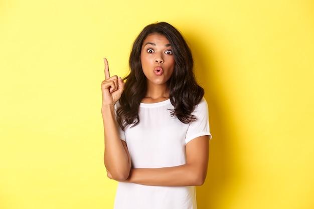 Portret van een slimme afro-amerikaanse vrouwelijke student die een oplossing heeft die een idee suggereert om de vinger op te steken en... Premium Foto
