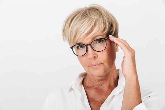 Portret van een slimme volwassen vrouw die naar de camera kijkt en haar bril aanraakt, geïsoleerd over een witte muur in de studio