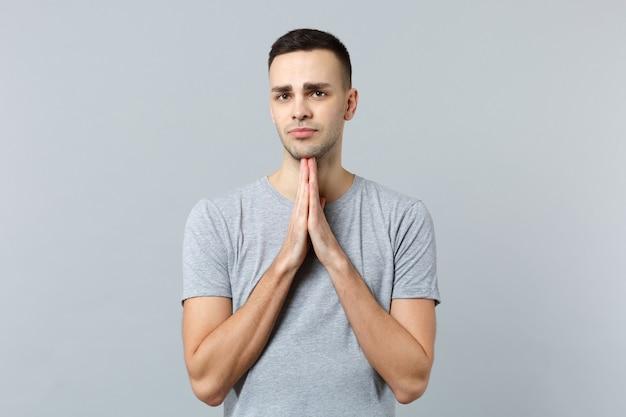 Portret van een smekende jongeman in vrijetijdskleding, zijn handen gevouwen, biddend