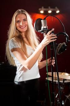Portret van een smileyvrouw die een microfoonstandaard houdt