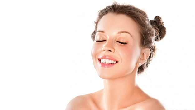 Portret van een smileyvrouw met gesloten ogen die op witte muur wordt geïsoleerd. gezond glanzend huid, tanden gezondheid en natuurlijke schoonheid concept