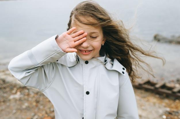 Portret van een smilling meisje in de buurt van de zee in de regenjas
