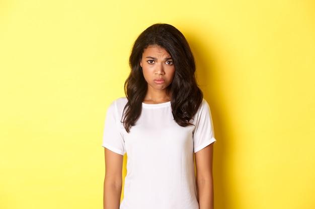 Portret van een somber en verdrietig afrikaans-amerikaans meisje dat mokkend en boos kijkt in een wit t-shirt