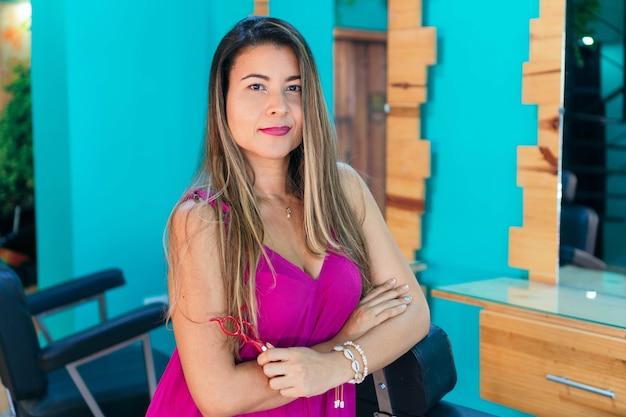 Portret van een spaanse vrouw bedrijfseigenaar die in een kapsalon staat. schoonheid en mode, persoonlijke verzorging.