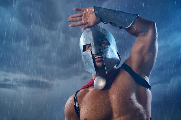 Portret van een spartaanse krijger die nat wordt in de regen en de hand opsteekt. close up van man in rode mantel en helm met waterdruppels poseren in donkere bewolkte atmosfeer buitenshuis. oud sparta, krijgersconcept.
