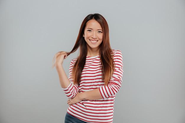 Portret van een speelse jonge aziatische vrouw die flirt