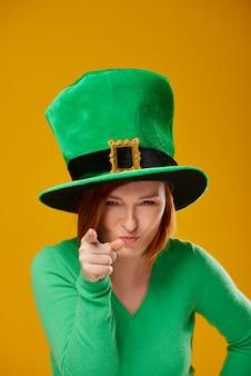 Portret van een speelse vrouw met de hoed van de kabouter wijzend op de camera