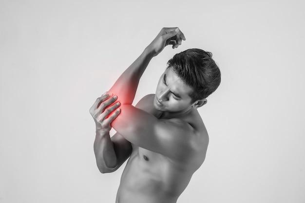 Portret van een spiermens die elleboogpijn heeft die op witte achtergrond wordt geïsoleerd