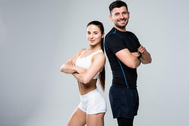 Portret van een sportief jong stel met armen gekruist op witte achtergrond