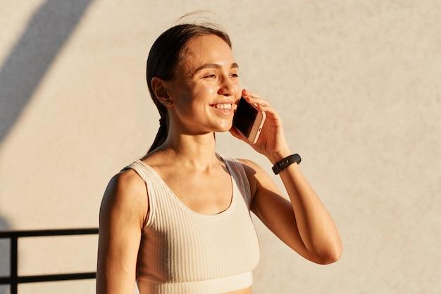 Portret van een sportief meisje dat op een smartphone in de buurt van een grijze muur praat, glimlachend in de verte kijkt, een witte top draagt, aangenaam nieuws hoort, geluk uitdrukt.