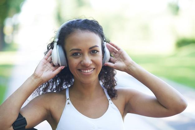 Portret van een sportieve jonge vrouw met koptelefoon