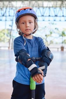 Portret van een sportieve voorschoolse jongen gekleed in casual kleding met beschermende uitrusting, hij blijft bij de scooter terwijl hij naar de camera buiten kijkt.