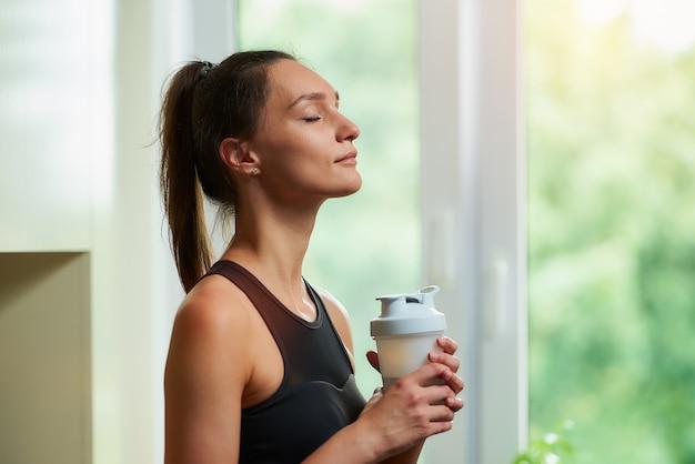 Portret van een sportieve vrouw die oefeningen thuis doet
