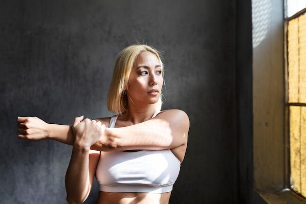 Portret van een sportieve vrouw die zich uitstrekt
