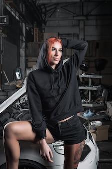 Portret van een sportieve vrouw in jeans en hoodie staat met gedemonteerde auto in de garage.
