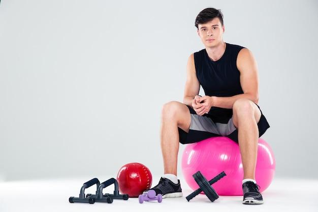 Portret van een sportman die op de fitnessbal zit geïsoleerd
