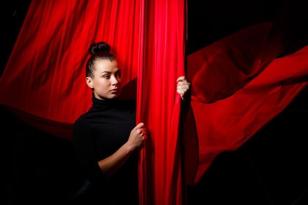 Portret van een sportmeisje op een achtergrond van rode doeken voor luchtgymnastiek. studio schieten op een donkere achtergrond,