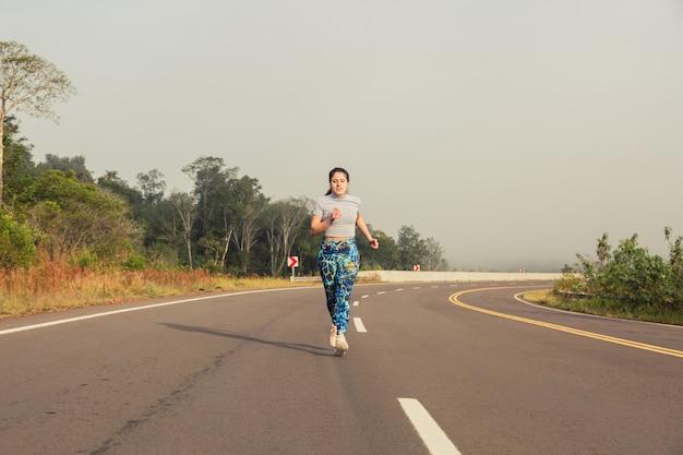 Portret van een sportvrouw die op de weg loopt