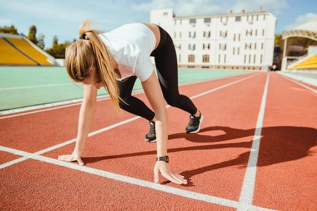 Portret van een sportvrouw die op het startsignaal wacht voor run at stadium