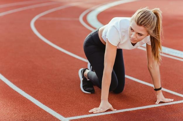 Portret van een sportvrouw die op het startsignaal wacht voor run