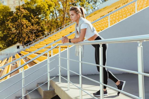Portret van een sportvrouw die zich bij openluchtstadion bevindt