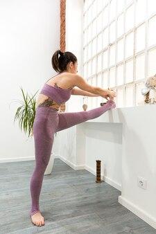 Portret van een sportvrouw die zich thuis uitstrekt. verticale weergave. ruimte voor tekst.
