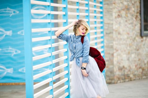 Portret van een staande glimlachende vrouw met kort blond haar, felroze lippen en naakt make-up leunend op blauwe en witte strepen hek
