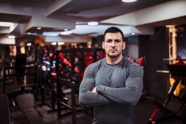 Portret van een sterke gespierde man in de sportschool, staande met zijn armen gekruist en kijken naar de camera.
